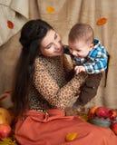 在秋天季节的家庭画象 妇女和小男孩坐黄色秋天叶子、苹果、南瓜和装饰 免版税库存图片