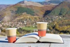 在秋天山的读的和饮用的咖啡 免版税库存图片