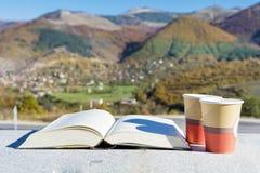 在秋天山的读的和饮用的咖啡 图库摄影