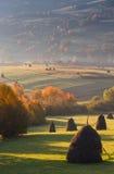 在秋天山草甸的阳光干草堆环境美化 免版税库存照片