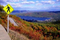 在秋天山顶部的行人交叉路标志与湖 免版税库存图片