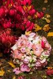 在秋天新娘花束的婚戒 免版税库存图片