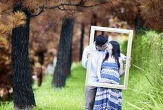 在秋天日的浪漫怀孕的夫妇 免版税图库摄影