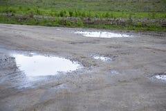 在秋天时间的泥泞的湿路 免版税库存图片