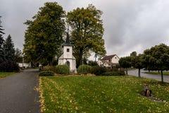 在秋天村庄中间的一个白色教堂 免版税库存图片