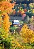 在秋天树中间的谷仓 免版税库存图片