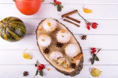 在秋天样式的自创烘烤 在一个木板的可口杯形蛋糕用肉桂条、茴香星、南瓜和莓果 库存图片