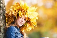 在秋天桔子的女孩画象离开花冠 库存照片