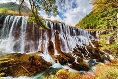 在秋天森林中的Nuo Ri郎瀑布Nuorilang 库存照片