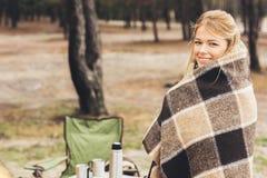 在秋天森林看的格子花呢披肩盖的美丽的少妇 免版税图库摄影
