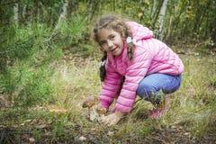 在秋天森林里一个小女孩发现了两牛肝菌蕈类 免版税图库摄影
