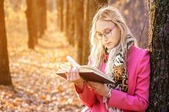在秋天森林里读书的美女 在树附近的妇女立场和读书 库存照片