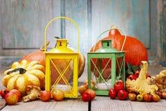 在秋天植物中的五颜六色的灯笼在木桌上 免版税库存图片