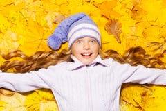 在秋天槭树叶子的愉快的女孩位置 库存图片