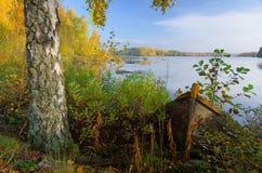 在秋天湖海岸的老木小船 免版税库存照片