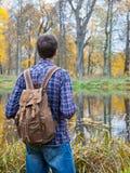 在秋天湖附近的男性远足者立场 库存照片