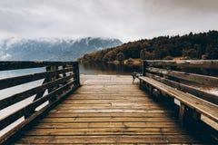 在秋天湖,秋天颜色的木码头 免版税库存图片