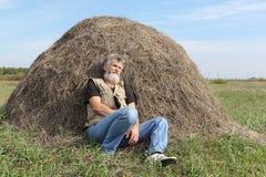 在秋天的一个干草堆附近供以人员睡觉在领域 免版税库存照片