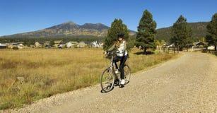 在秋天的妇女骑自行车者乘驾 免版税库存图片