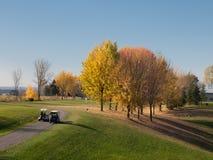 在秋天的高尔夫球与驾驶购物车的人 图库摄影