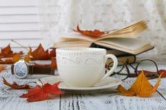 在秋天秋天的咖啡杯离开和木表面背景 图库摄影