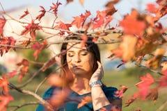 在秋天红色后的年轻美丽的十几岁的女孩在树离开 免版税库存图片