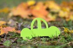 在秋天背景的绿色汽车 友好的Eco 免版税图库摄影