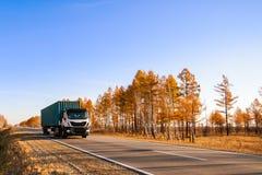 在秋天路的白色半卡车 免版税库存图片