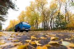 在秋天路的蓝色卡车 库存图片