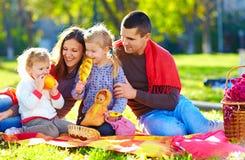 在秋天野餐的愉快的家庭在公园 免版税库存图片