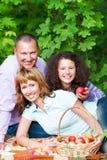 在秋天野餐的愉快的年轻家庭 免版税库存照片