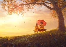 在秋天阵雨下的孩子 免版税库存图片