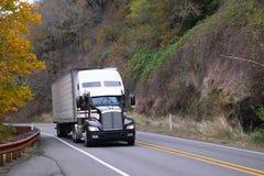 在秋天高速公路的黑白半卡车收帆水手拖车 图库摄影