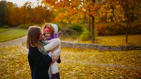 在秋天,当黄色在使用的妈妈和的女孩附近离开与槭树叶子,笑和微笑 妈妈拥抱和戏剧 股票视频