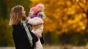 在秋天,当黄色在使用的妈妈和的女孩附近离开与槭树叶子,笑和微笑 妈妈拥抱和戏剧 股票录像