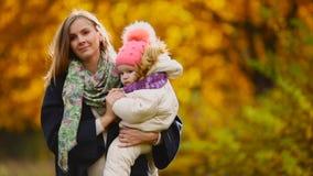 在秋天,当黄色在使用的妈妈和的女孩附近离开与槭树叶子,笑和微笑 妈妈拥抱和戏剧 影视素材