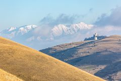 在秋季的第一雪:城堡和白色山 免版税库存图片