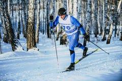 在种族期间的特写镜头年轻运动员滑雪者在森林古典样式 免版税图库摄影