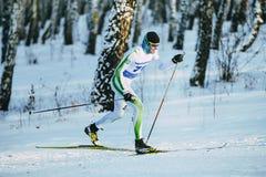 在种族期间的男性运动员滑雪者在森林经典样式小山攀登 免版税库存图片