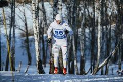 在种族期间的年轻男性滑雪者在上升森林 免版税库存照片