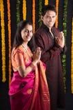 在种族穿戴的印地安年轻夫妇在namaskara摆在 免版税库存照片