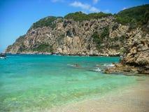 在科孚岛海岛、在绿色植被和岩石峭壁的Paleokastritsa盖的希腊、海滩 蓝色和绿松石江边 图库摄影