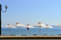 在科孚岛遮阳伞和灯的Ipsos海滩 免版税图库摄影