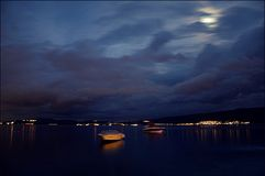 在科托尔海湾的水的一条黄色小船在与岸灯笼和月亮的反射的晚上在云彩 库存图片