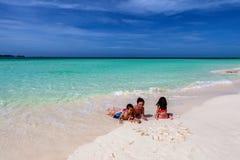 在科科岛照顾和她的使用在白色含沙古巴海滩的孩子 免版税库存照片