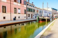 在科马基奥五颜六色的意大利村庄的运河的小船  免版税库存照片