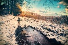 在积雪的乡下公路的壮观的日落 库存照片