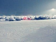 在积雪的停车场的红色尾灯 库存图片