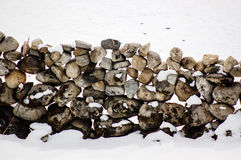 在积雪的地面的石墙 免版税库存图片
