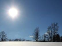 在积雪的小山的明亮的太阳 免版税库存照片